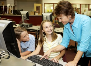 A helpful teacher showing school kids how to use the computer.